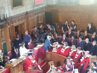 Elizabeth Hurley and extras in the council chamber filming The Royals
