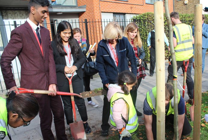 Students planting trees outside Featherstone High School