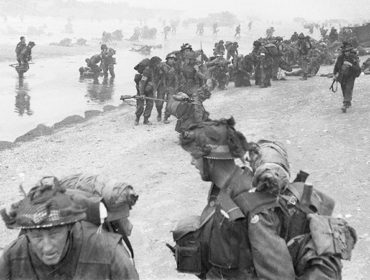 British Forces during the Invasion of Normandy 6 June 1944 Troops of 3rd Infantry Division on Queen Red beach, Sword area, circa 0845 hrs, 6 June 1944. In the foreground are sappers of 84 Field Company Royal Engineers, part of No.5 Beach Group, identified by the white bands around their helmets. Behind them, medical orderlies of 8 Field Ambulance, RAMC, can be seen assisting wounded men. In the background commandos of 1st Special Service Brigade can be seen disembarking from their LCI(S) landing craft.