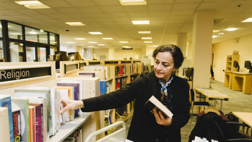 Volunteer stacking shelves at West Ealing Library as it prepares to be community managed