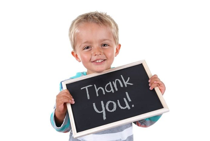 Child holding thank you on a chalk board