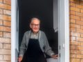 Elderly man opens door