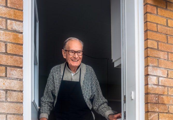 Elderly man opens door
