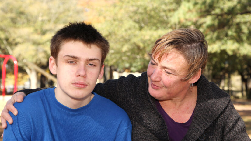 Mother comforts teenager