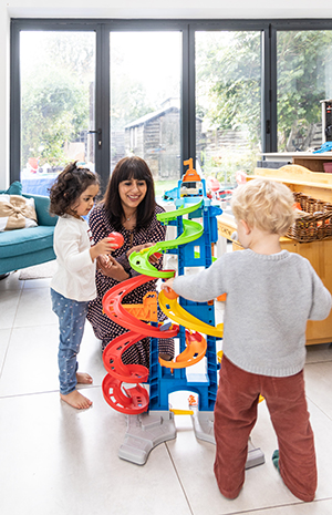 Simmi Bajaj, co-founder of Ealing Toy Library, playing with one of the toys with one of her daughters and friends
