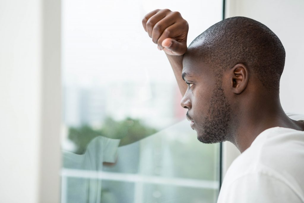 mental health - man looking thoughtfully out of a window